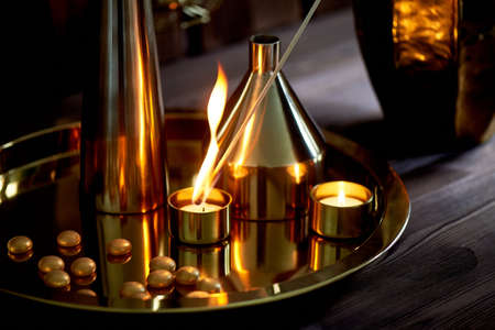 Hand lights a candle with a long match with a bright flame.The warm Golden gamma. Evening comfort. Many vases of different shapes of gold metal.