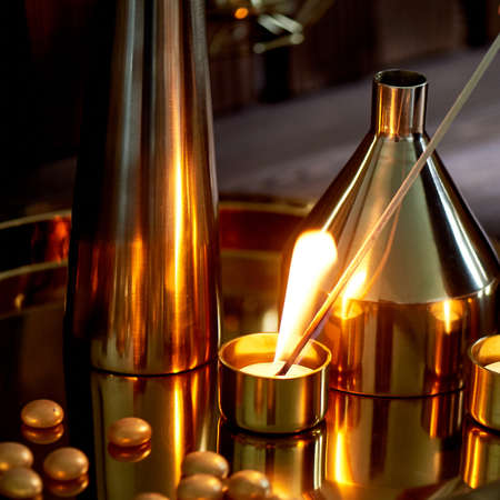 Hand lights a candle with a long match with a bright flame.The warm Golden gamma. Evening comfort. Many vases of different shapes of gold metal. Foto de archivo - 123525318