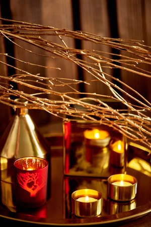 Cozy decor. Gold and red. Burning candles, Golden vessels Foto de archivo - 123525319