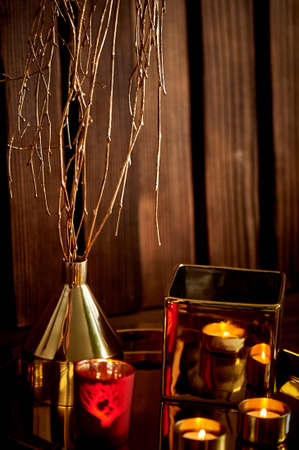 Cozy decor. Gold and red. Burning candles, Golden vessels Foto de archivo - 123525320