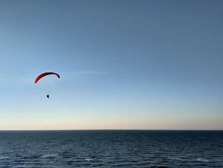 Paraglider flies over the sea before sunset.Expanse. Air sports.