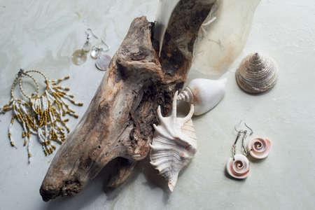 Meereskollektion auf grauem Marmorhintergrund. Muschel- und Perlmuttohrringe. Sommer Schmuck.