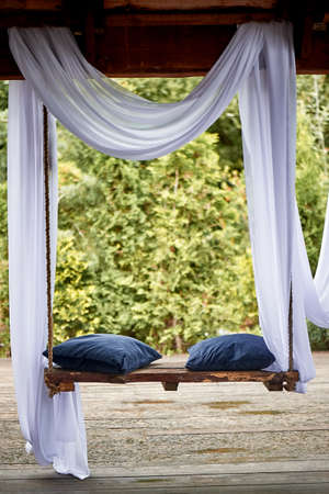 Wooden swing in the garden, with blue soft cushions. A cozy place to relax
