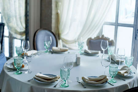 Classic table setting at the Banquet. Glasses of light green glass. wedding Banquet. Stock Photo