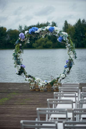 Round arch with white and blue flowers. Check-out on the river or lake. Wedding registration. Stock Photo