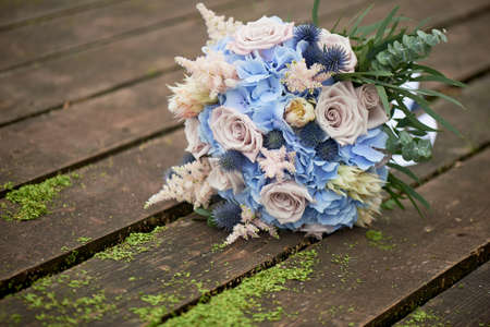 Bouquet of the bride with a powdery rose and blue hydrangea. Wedding florist.