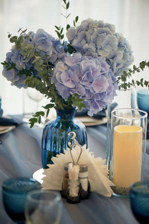 Wedding decoration of the Banquet hall for the wedding in blue. Hydrangea.Blue glasses Stock Photo