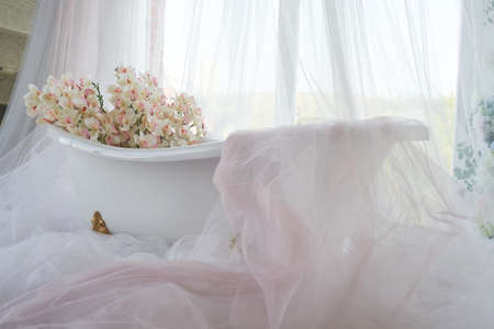 Lots of orchids and chiffon in the snow-white bath on the paws. Bathroom.