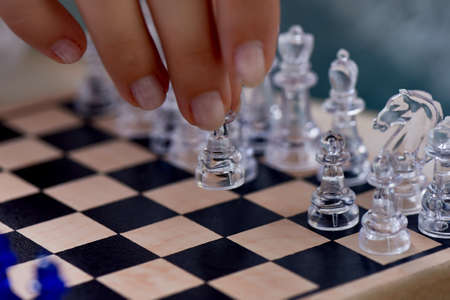 A womans hand moves the pieces on the chessboard. Finding solutions, brain activity. The development of the mind. 写真素材 - 129976106
