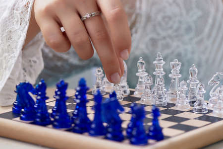 A womans hand moves the pieces on the chessboard. Finding solutions, brain activity. The development of the mind.