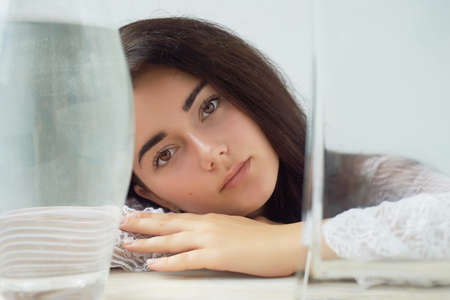 A girl with dark eyebrows , brown eyes and dark hair. Natural beauty. Thick wide eyebrows. Vessels with water. Natural beauty Stock Photo