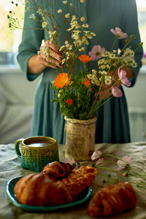 The girl makes a bouquet of wildflowers, rearranges them in a vase. Village house. Coffee and croissants