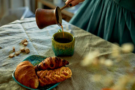 A womans hand pours coffee brewed in Turk. Rustic simplicity.