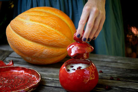 Red ceramic, handmade. Shaped like a grenade.Female hands, open the lid over the pot of porridge. Healthy and delicious Breakfast.