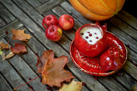 Red ceramic, handmade. Shaped like a grenade.Pot with porridge, autumn leaves and juicy orange melon. Wholesome breakfast