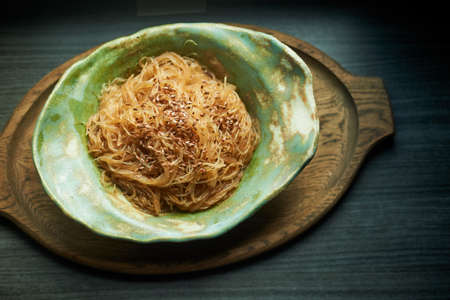 Cellophane with sesame seeds with sweet and sour sauce. In a deep ceramic bowl handmade. Appetizing dish