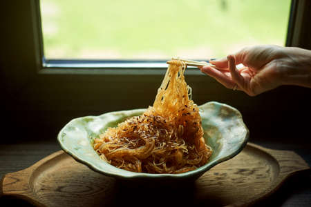 Cellophane with sesame seeds with sweet and sour sauce. In a deep ceramic bowl handmade. Appetizing dish.Female hand, with sticks. Stock Photo