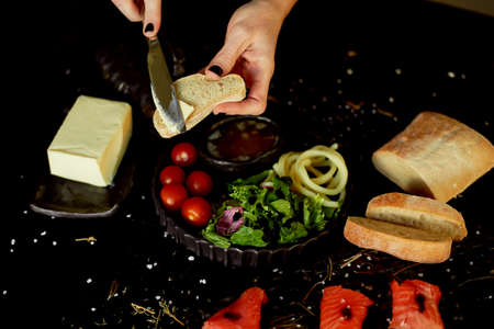 Tasty and healthy food. Black background, handmade pottery.A womans hand with a dark manicure can butter on a piece of ciabatta.