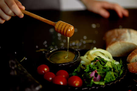 Tasty and healthy food. Black background, handmade pottery.Hand raises a spoon for honey. Honey flows down. Beautiful color