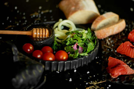 Tasty and healthy food. Black background, handmade pottery.