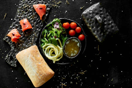 Tasty and healthy food. Black background, handmade pottery.Table with delicious and nutritious food . Cecil cheese, arugula, honey, red fish and cherry tomatoes. Healthy food.