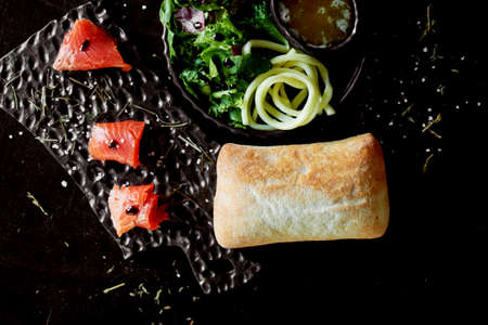 Tasty and healthy food. Black background, handmade pottery.Table with delicious and nutritious food . Pieces of red fish and ciabatta. Healthy food.