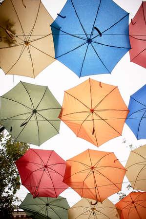 Textur. Viele Regenschirme hängen gegen den Himmel. Schutz vor Sonne und Regen. Rot, Orange und Blau.