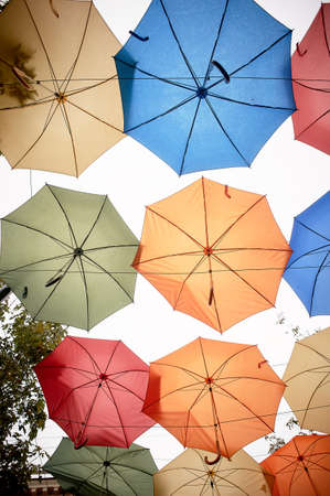 Texture. Lots of umbrellas hanging against the sky. Protection from sun and rain. Red, orange and blue.