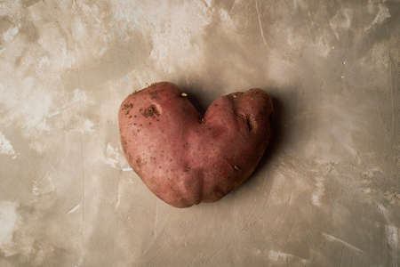 Ugly food, potatoes in the shape of a heart. Natural and simple farm products.