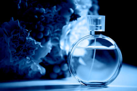 A round bottle of perfume on a dark background, near a bouquet with pink flowers. Aromatherapy and perfumes.Classic blue. The 2020 trend. Stock Photo
