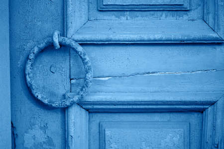 Old vintage door with peeling paint and a rusty handle in the form of a ring, Classic blue. The 2020 trend. Foto de archivo