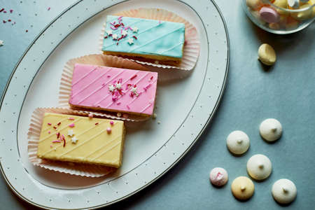 Beautiful delicate shortbread cakes with icing of delicate colors. Tea party for the holiday. Confectionery art. The view from the top, the background is silver.