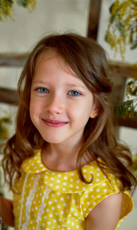 Portrait of a smiling girl in a yellow dress 6 years old. Pierced ear. Blue eyes, long hair.