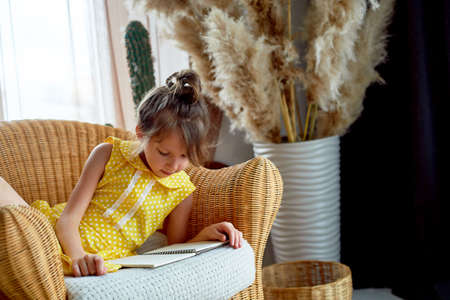 Girl, 6 years old. Her hair was pulled back in a bun. She reads the book with pleasure. Yellow dress, beautiful interior. Craving for learning, love for reading.