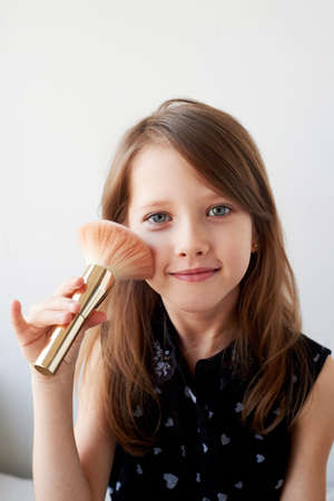 The girl is 6 years old on a light background, powders her cheeks with a brush. Striving for beauty, mothers cosmetics.