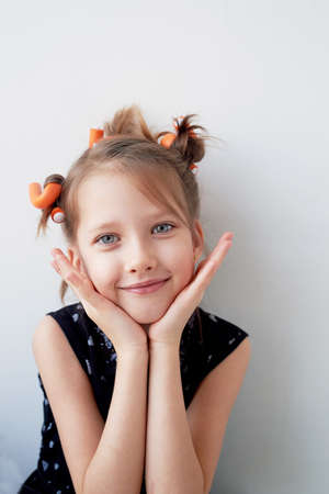 A 6-year-old girl with curlers on her head. The pursuit of beauty.Childrens joys. Isolated on a white background.