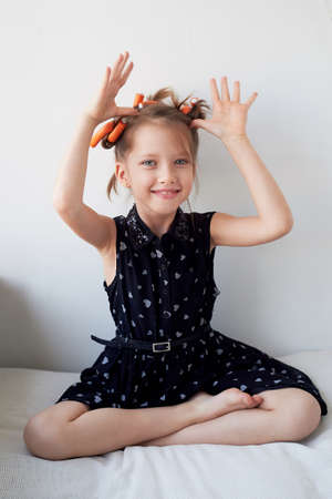A 6-year-old girl with curlers on her head, fooling around. The pursuit of beauty. Childrens joys. Isolated on a white background.