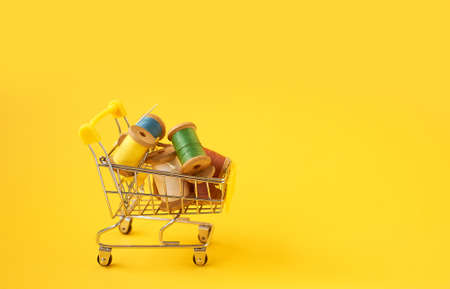 Colored coils with threads on a yellow background.Handicrafts and sewing.Shopping cart, online shopping.