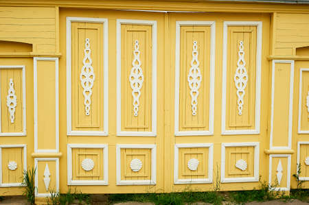 Wooden wide gates in old Russian houses. Figurative ornaments made of wood. Bright colors. Ancient wooden Russian houses.