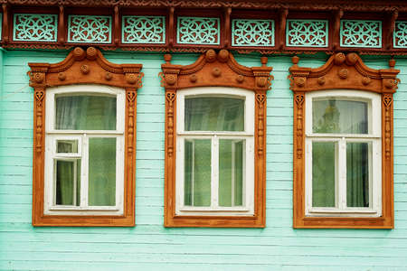 Old wooden houses with beautiful windows. Frames with tiles. An old Russian house.