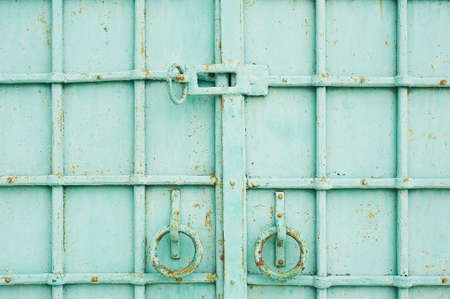 The metal gates are turquoise. With round rings handles. Metallic decorative forging.