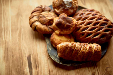 Bake on a plate. On a wooden background. Free space for text on the left. A wicker with jam.