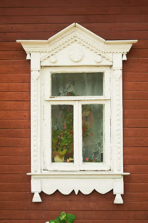 A window with tiles in an old wooden Russian house. Historic center. Beautiful window design.