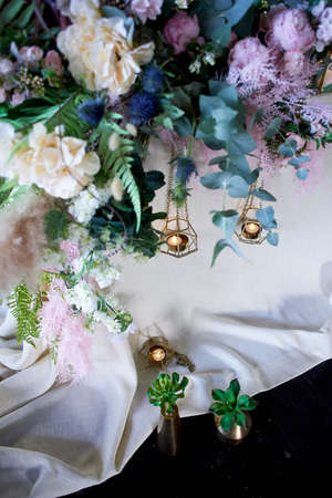 Wedding decoration, floristry.Succulents in gold vessels near the table with a light tablecloth. Standard-Bild