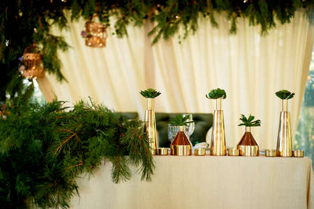 Decoration of the bride and grooms table in eco style. Golden vessels with succulents, linen tablecloth, spruce branches.
