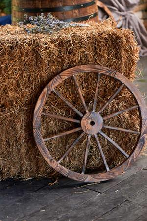 An old wooden wheel from a cart near a haystack. The village, the village decor. Standard-Bild