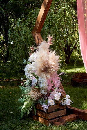 Part of the wedding wooden arch at the exit check-in. Wedding in nature. Composition of pampas, fern and dried flowers.