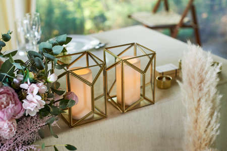 Glass candlesticks with gold metal trim on a decorated wedding table. Two big candles. Standard-Bild