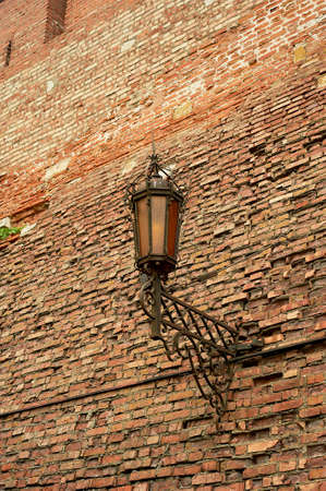 An ancient forged lantern on a red brick wall. Ancient fortress, history.