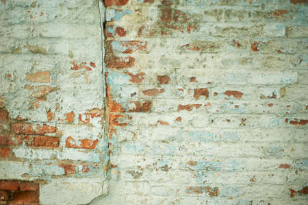 Wall with painted brick and peeled paint. Texture. Abandonment.